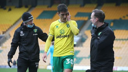 Dimitris Giannoulis of Norwich leaves the match with a head injury after a clash with Joe Rankin-Cos