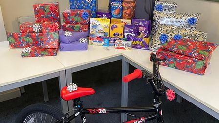 Wrapped presents piled up on a table and a bike.