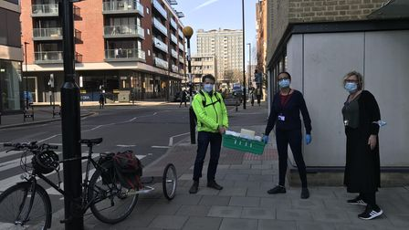 Clerkenwell Mutual Aid co-ordinator George Allan (left) being given a food parcel by volunteers at the St Luke's Foodbank