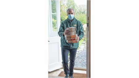 Delivery man at front door with food parcels