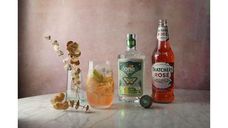 A picture of Thatchers Rose cider on a table with a cocktail glass and a bottle of One gin