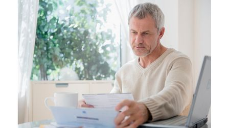 Mature man looking at paperwork for pension commencement lump sum (PCLS)