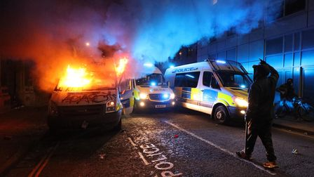 A vandalised police van on fire outside Bridewell Police Station, as other police vehicles arrive af