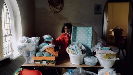 Beautine Wester sorts through donations in the back of the Clapton Seventh Day Adventist Church, Hackney