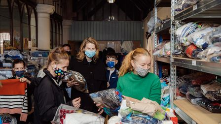 Volunteers from Clapton CFC, a local women's football club, go through clothes donated to the E5 Bab