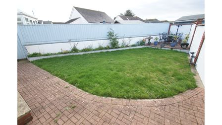 The rear garden features a block paved patio, lawn with flower bed border and a further patio seating area.