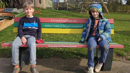 Roundwood Primary colourful friendship bench with a pupil sat at either end