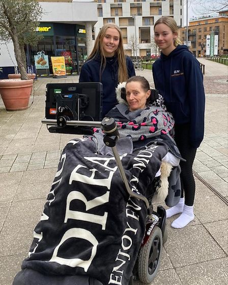 Two teenage girls in blue tracksuits and an older woman in a wheelchair pose for a photo.