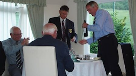 In the club house after the match, Captain John Bainbridge presents a bottle to the Taunton Captain.