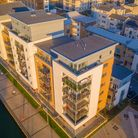 Aerial shot of Mizzen Court, Portishead. High-rise apartment complex with orange, blue and cream render on harbourside.