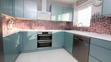 Modern kitchen with teal acrylic units and white worktops, built-in oven, appliance and red and pink mosaic tiles