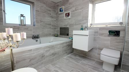 Fully-tiled beige modern bathroom with bath, off-floor basin in cabinet and toilet. Mizzen Court, Portishead.
