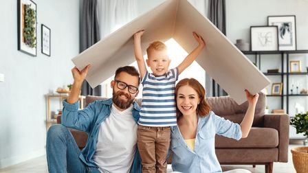 Parents and son holding model roof in home