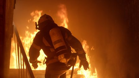 A firefighter runs upstairs in a burning building.
