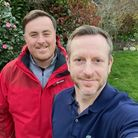 Neil Turnbull and Chris Reilly standing outside on grass smiling