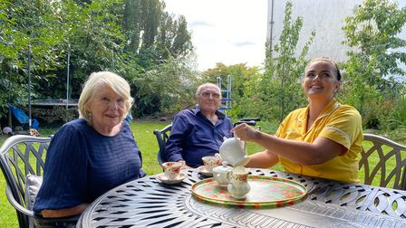 Three people sat having a cup of tea