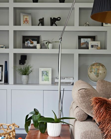Shelving in grey in living room with treasured possessions on display