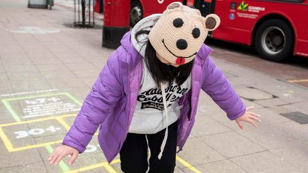 Young child plays hopscotch neat London street.