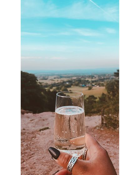 View of Cheshire countryside from Alderley Edge's The Edge, with woman holding a glass of prosecco