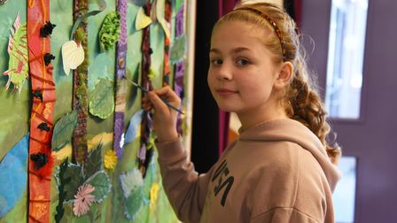 Lily with the painting at Dale Hall Primary School