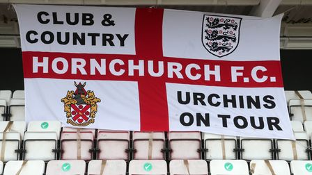 A Hornchurch FC flag hangs in the stands at Bridge Avenue