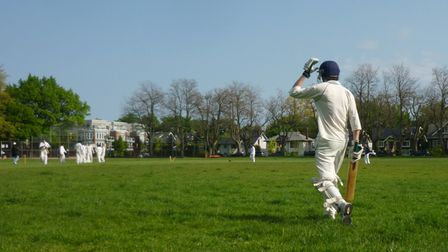 A batsman walks out on to a cricket pitch, ready to play