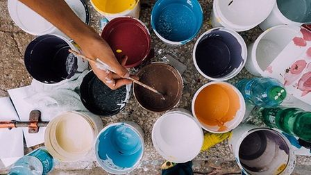 Pots of different coloured paints with someone dipping a paintbrush into one of them