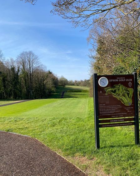 Sign in the foreground denoting hole, tree lined fairway