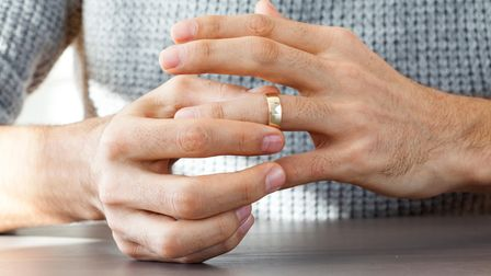 Man taking off wedding ring and considering getting a divorce