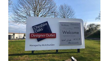 A sign on field that reads welcome to Cheshire Oaks