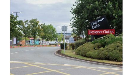 A road leading into Cheshire Oaks with a sign in bush reading Cheshire Oaks designer outlet