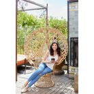 Maggie Colette sat on wicker chair, smiling, holding mobile phone