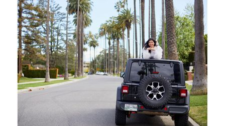 Maggie Colette, poking head out of a jeep on the road