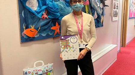 School pupil holding donated activity packs