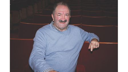 Theatre owner dressed casually sat in seats