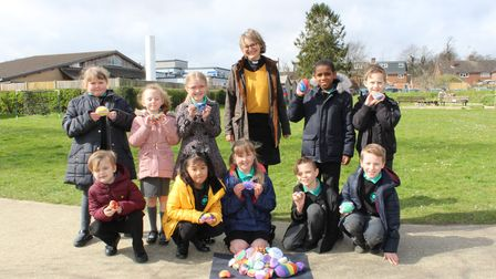 Children from Dunmow St Mary's School with their painted cairn stones, and Rev Elsie of St Mary's Church, Great Dunmow