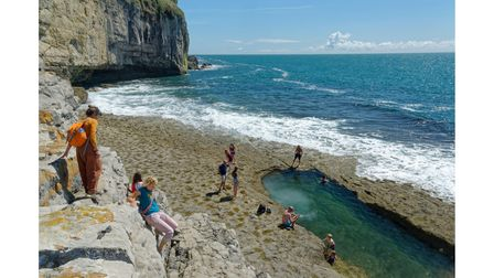 People climbing down to the swimming pool blasted into Dancing Ledge