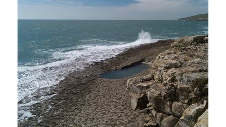 The swimming pool at Dancing Ledge showing the pitted rock platform that makes the waves appear to dance