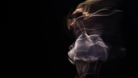 Blurred movements of a dancer on a black background, representing the Invisible Dances project coming to Dorset