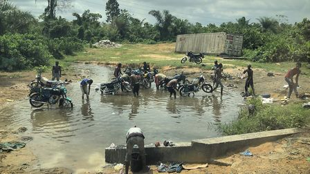 Men wash their motorbikes in a water hole near the border of Anglophone region in Cameroon.Picture: