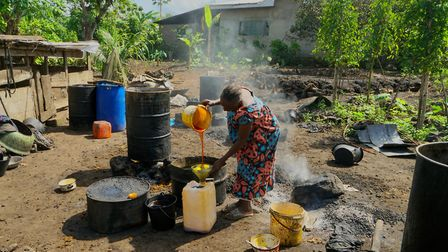 A elderly resident of Muama village, located in SW Cameroon, pours some homemade palm oil into a con