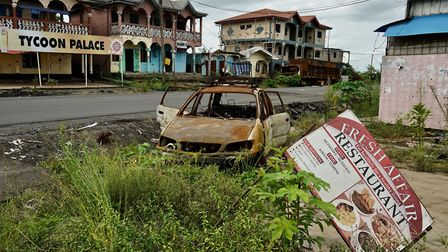 A destroyed car and buildings in a small town on the main highway near Buea. Picture: Giles Clarke/U