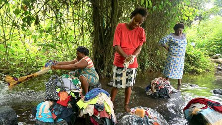 Women displaced from rural villages in Anglophone region gather to wash clothes in a bush stream in