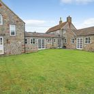 The back view of a stone-built sprawling cottage in North End Road, Yatton with a lawn in front.