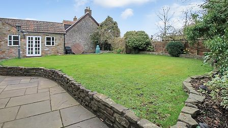 Lawned garden of the cottage in North End Road, Yatton with pathway on left and low stone wall leading to the property'sback