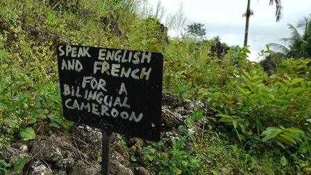"A sign saying "" Speak English or French for a bilingual Cameroon"" outside a now abandoned school in"