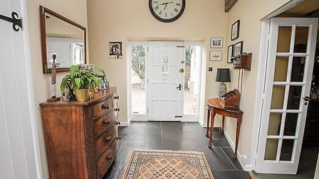 Magnolia hallway with white door at back of picture with glazed side panels, slate-effect flooring and sideboard on left.