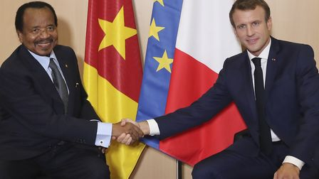 French President Emmanuel Macron (R) shakes hands with Cameroon President Paul Biya prior bilateral