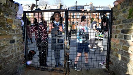 Children at the closed gate of St Joseph's Church in Highgate