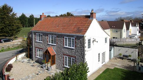 Stone and white render detached cottage in Worlebury Hill Road, Weston with front and side gardens.